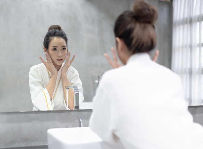 Facial Beauty.Young beautiful Asian woman applying moisturizer cream on her pretty face and looking to mirror at bathroom.Natural skin care and people Concept.