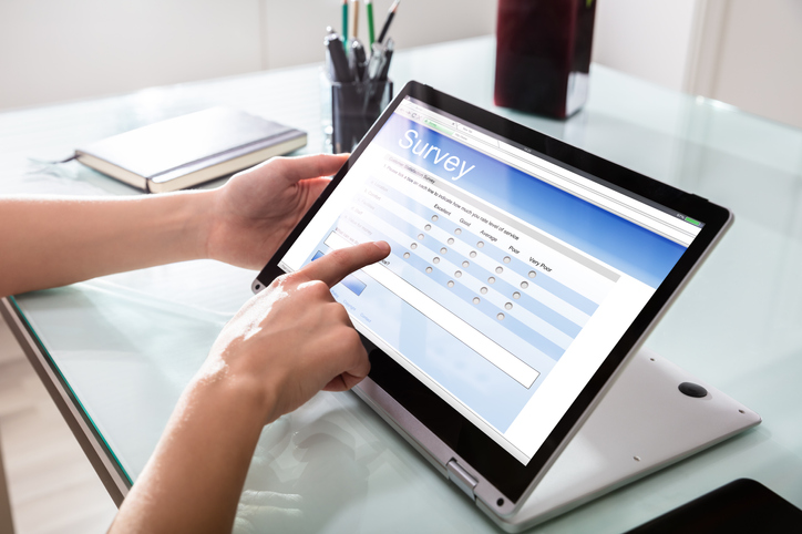 Close-up Of A Customer Hand Filling Online Survey Form On Digital Laptop In Office