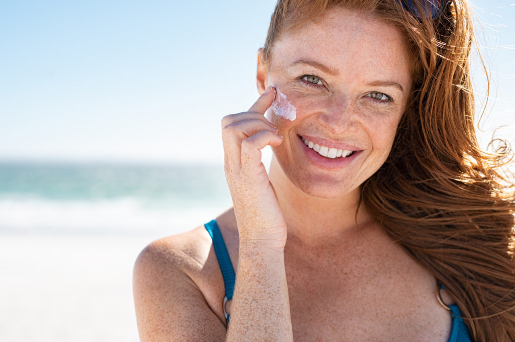 Red hair woman with freckles putting on sunscreen at beach