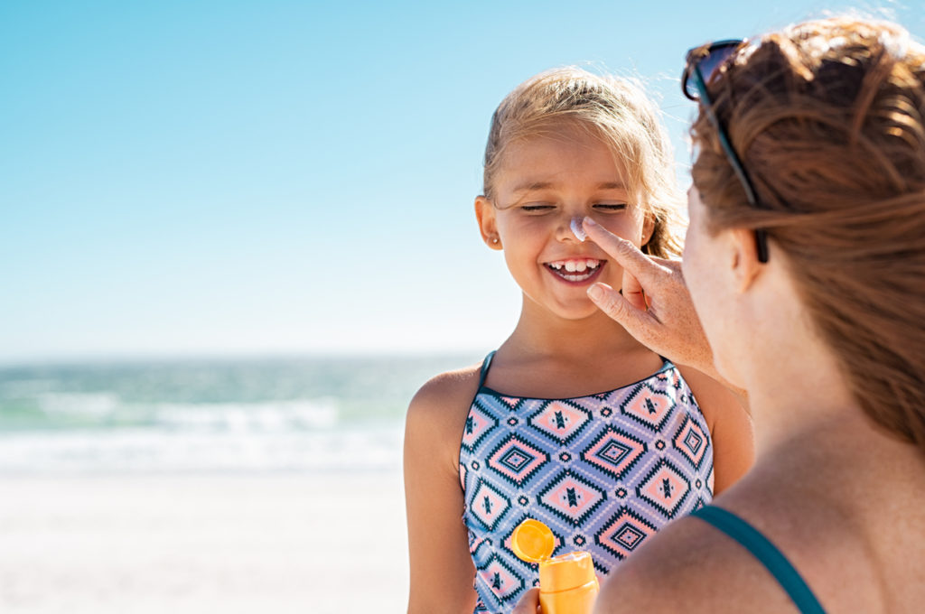 Young mother applying protective sunscreen on daughter nose at beach.