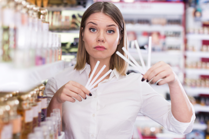 Girl holding testers in cosmetics shop