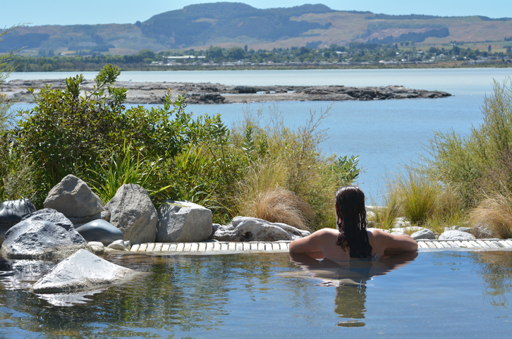 Young woman having a spa in outdoors hot pool in Rotorua, New Zealand.