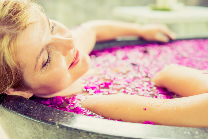 Close-up photo of woman relaxing in flower bath